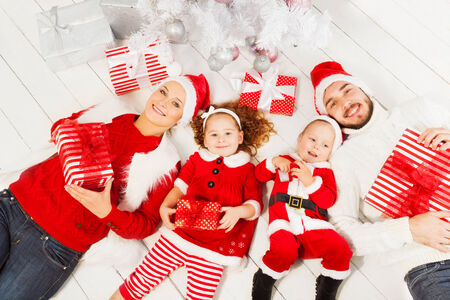 Mom dad and kids with present under Christmas tree photo
