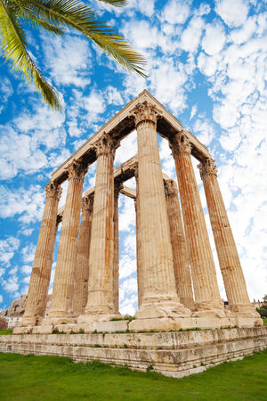 cultural history: Beautiful view of Zeus temple on green grass with palm leaves with sky background in Athens, Greece during summer time Stock Photo