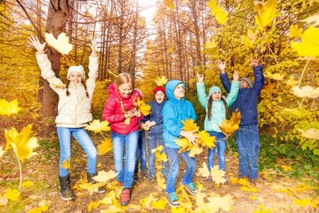 Excited kids play together with flying leaves photo