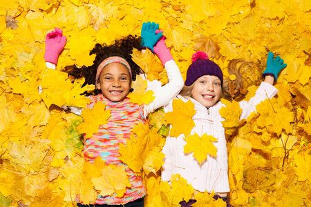 African and Caucasian girl covered in maple leaves photo