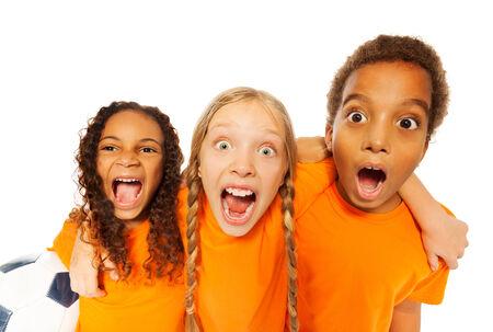 kids hugging: Screaming happy soccer team kids