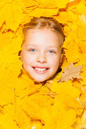 8 years: Face of a little blond girl in autumn leaves Stock Photo