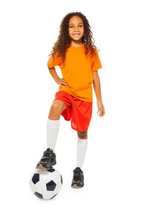 かわいい黒の女の子がスタジオでサッカー ボールの上に立つ