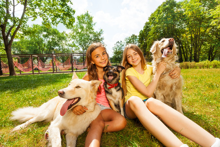 dogs sitting: Two teenage girls sitting with three dogs in park Stock Photo