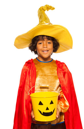 Boy in wizard costume with candy Halloween bucket photo