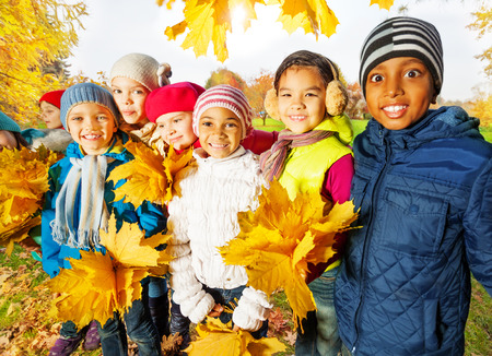Happy children with bunches of yellow maple leaves