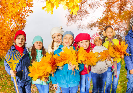 kid rake leaves. row of happy kids with rake and leaves bunches photo kid