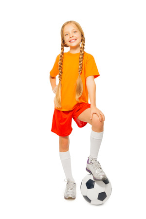 girl in sportswear: Cute blond girl stand on soccer ball in studio Stock Photo