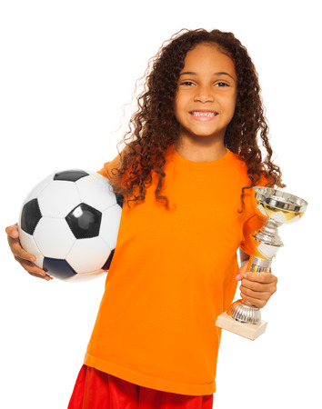 eight years old: Little black girl holding soccer ball and prize