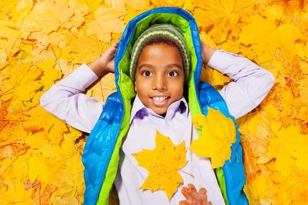 garcon africain: Garçon africain réside dans tas de feuilles d'automne