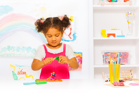 Preschool girl play with modeling clay in class photo