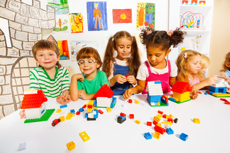 Many kids play with plastic blocks in classroom