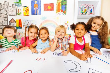 Dzieci: Grupa dzieci, chłopców i dziewcząt w klasie czytania Zdjęcie Seryjne