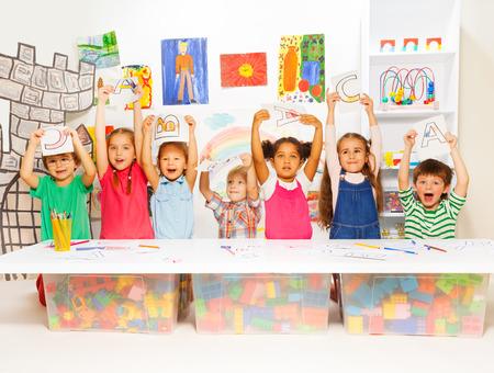 niños escribiendo: Grupo de niños pequeños en el desarrollo de la primera lección