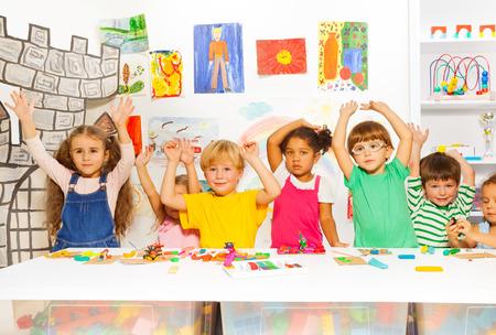 ni�os estudiando: Felices los ni�os con plastilina en la clase de jard�n de infantes Foto de archivo