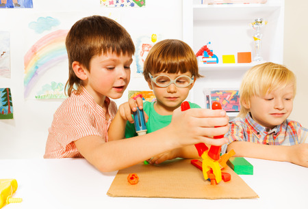 Little boys with toy pliers in classroom photo