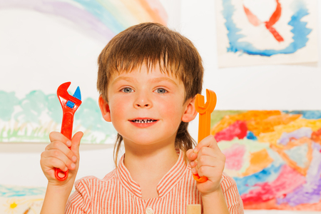 Close portrait of happy boy holding wrenches photo