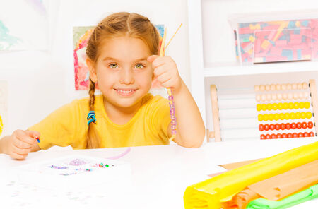 accessorize: Little beautiful blond girl puts beads on string