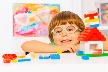 little table: Close portrait of boy in glasses with blocks
