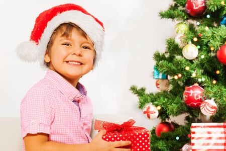 Nice little boy in Santa hat with present smiling photo
