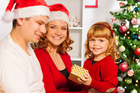 Family with little girl open presents on Christmas photo
