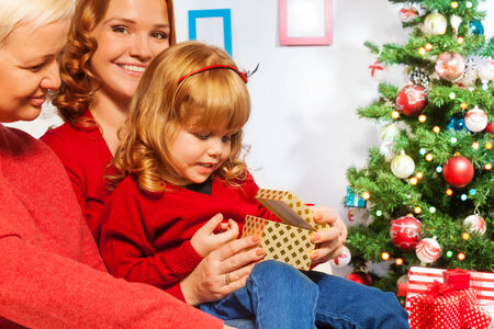 Little girl open presents with mother and granny photo
