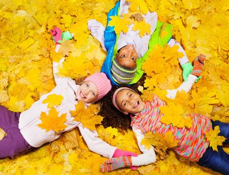 Kinderen spelen met de herfst esdoorn oranje bladeren Stockfoto