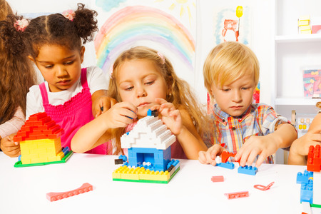 kindergarden: Several beautiful clever kids boys and girls playing with plastic blocks constructing houses in the kindergarten class Stock Photo