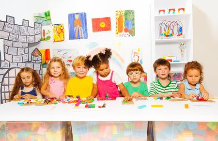 Grote groep van diverse zoek voorschoolse jongens en meisjes spelen met boetseerklei in de klas in de kleuterschool