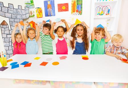 niños felices: Grupo de Kindergarten de pequeños niños, los niños y niñas diversa busca la celebración de formas de cartón junto a la mesa en el jardín de infancia con la decoración y dibujos en el fondo