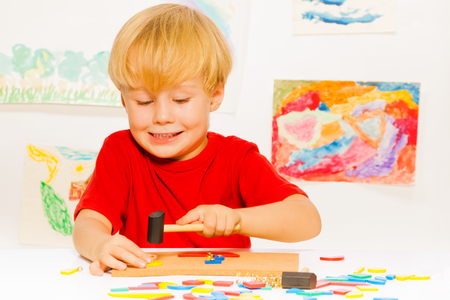 nailing: Cute little blond boy play with game nailing blocks to the plank with hammer smiling, sitting by the table in kindergarten class