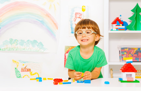 constructing: Portrait of clever looking little preschool boy in glasses playing with plastic blocks constructing simple house in the room background