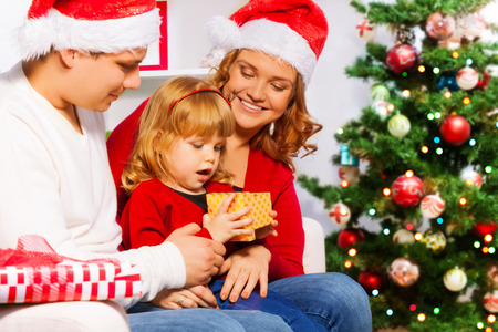 three years old: Family with mom dad and little three years old daughter sitting near Christmas tree and opening New year presents surprised little girl
