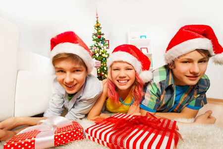 santa cap: Three happy teen kids laying on the floor in the living room near Christmas tree in Santa caps smiling and laughing with red presents