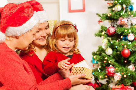 Mother and grandmother giving present to daughter photo