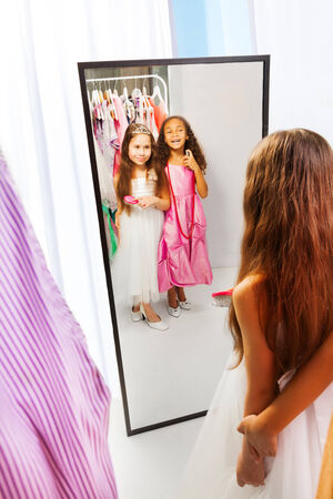 Twee kleine meisjes met jurken in de spiegel Stockfoto