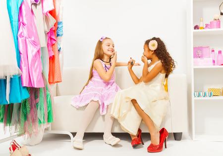 小さなアフリカの女の子は彼女の友人に化粧を置く 写真素材