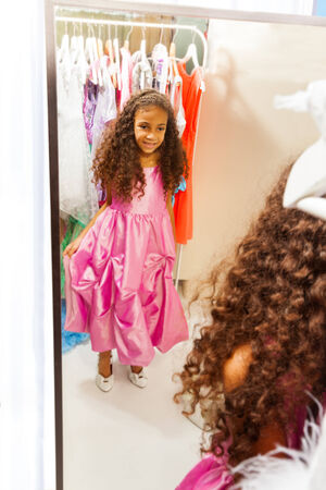 Little African girl try on dress before mirror photo