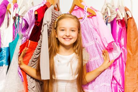 Schattig meisje staande tussen hangers tijdens het winkelen
