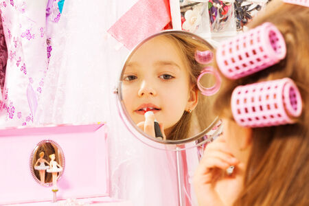 jewel case: Cute girl making up her face looking in mirror Stock Photo