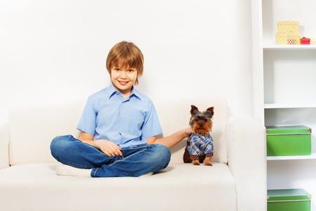 yorky: Charming brown Yorkshire Terrier with boy on sofa Stock Photo