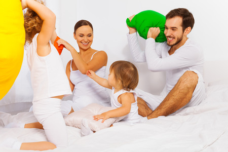 family fight: Father, mother and kids play with colorful pillows