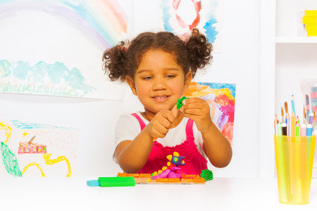 Little Hispanic looking girl play with plasticine photo