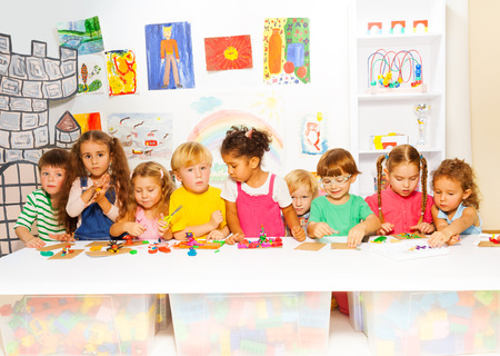 Large group of kids play with plasticine in class