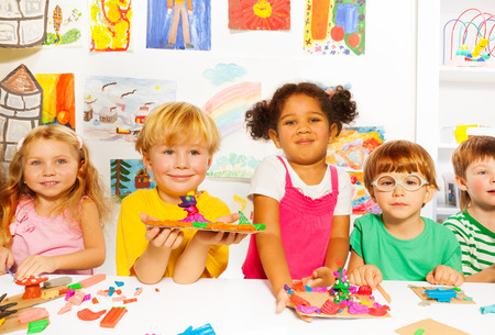 crafts person: Happy kids with modeling clay in classroom