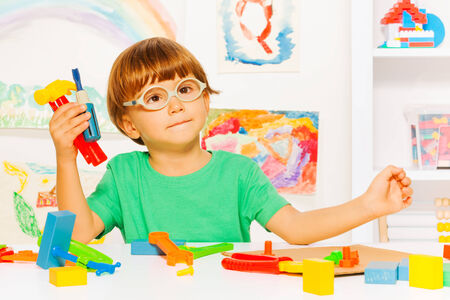 Smart boy with plastic tools in classroom photo