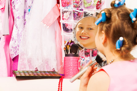haircurlers: Small smiling girl with hair-curlers, face brush