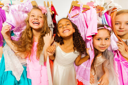 clothes on hangers: Laughing girls standing among colorful dresses
