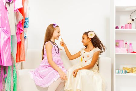 kids dress: African girl applying perfume  on her friend