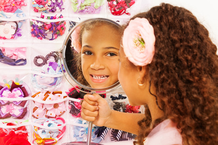 reflects: Beautiful small African girl reflects in mirror